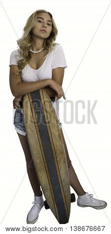 Beautiful blond girl wearing white shirt and jean shorts leaning on skateboard on white background.