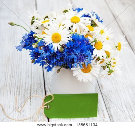 daisies and cornflowers in vase on a old wooden table