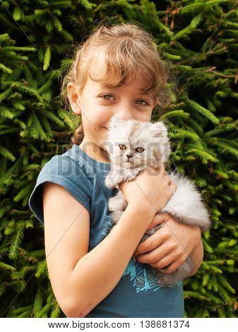 Little girl hold kitten of persian cat
