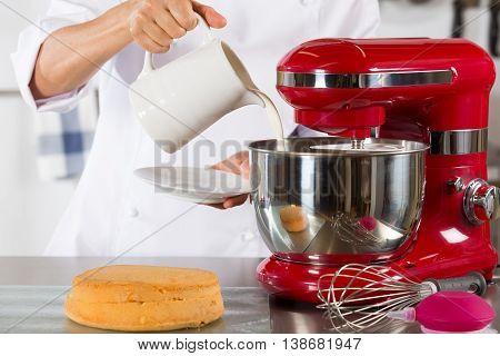 Chef preparing whipping cream to make a cake