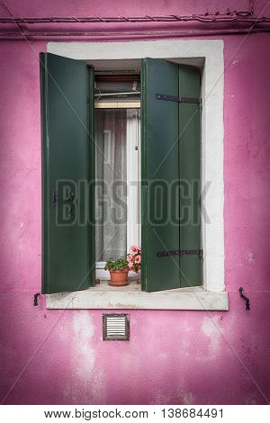 Picturesque old window with dark green shutters on pink wall with vignette effect (Burano island Venice Italy)