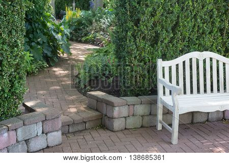 A whitewashed bench sits near a brick walkway as it winds into the distance.