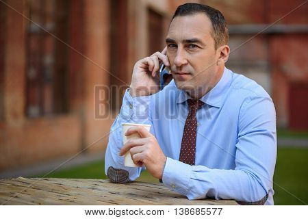 Serious middle-aged businessman is making break after work. He is sitting at table outdoors and drinking coffee. Man is talking on mobile phone and looking at camera with confidence