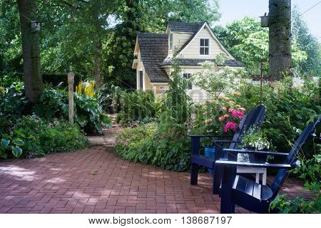 A charming playhouse is seen beyond two wooden chairs in a shaded garden patio.
