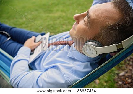 Relaxed businessman is listening to music from headphones. He is lying on hammock in park. His eyes are closed with pleasure