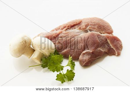 a piece of meat, white background, parsley, tomatoes and mushrooms