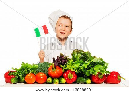 Funny kid boy in cook's uniform holding flag of Italy, standing behind the table full of fresh vegetables, isolated on white