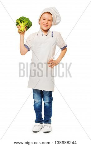 Full-length portrait of happy kid boy in cook's uniform holding fresh broccoli, isolated on white