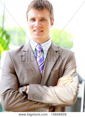 Happy businessman standing with hands in pocket in front of windows, looking at camera, smiling