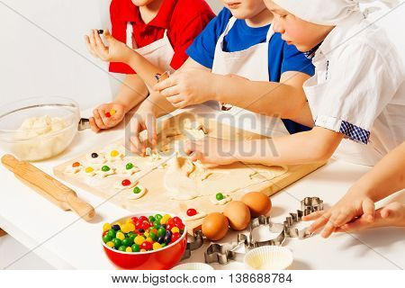 Kids in white aprons making candy filled cookies with cookie cutters on wooden desk