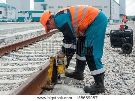 Tobolsk, Russia - July 15. 2016: Sibur company. The worker establishes jack for lifting rails for the purpose of repair of a railroad body