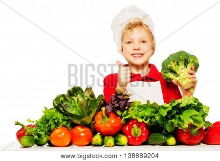 Cute boy in cook's showing thumbs up sign, holding fresh broccoli, isolated on white