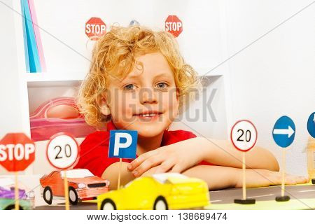 Smiling fair-haired preschooler playing driver with toy cars and road signs in the kindergarten