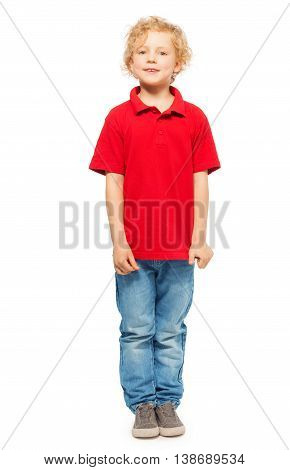 Full-length portrait of blond curly-haired kid boy in red polo shirt and denim, isolated on white