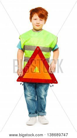 Full-length portrait of redheaded five years old boy, wearing high visibility vest and holding warning triangle, isolated on white