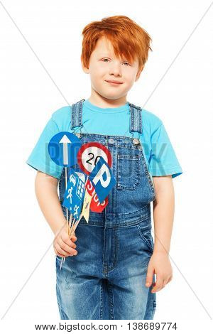 Redheaded five years old boy in blue t-shirt and overall, holding set of toy road signs, isolated on white
