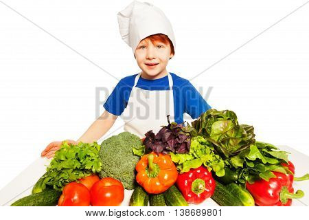 Redheaded kid boy in cook's uniform preparing healthy meal with fresh vegetables, isolated on white