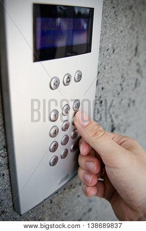 Close up of finger pressing button on intercom numpad