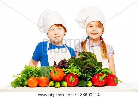 Two kids, redheaded boy and blond girl in cook's uniform, preparing fresh vegetables for healthy meal, isolated on white background