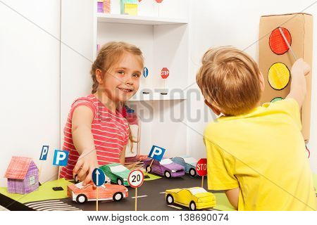Happy five years old girl playing with car model while boy pointing to stop signal of the light