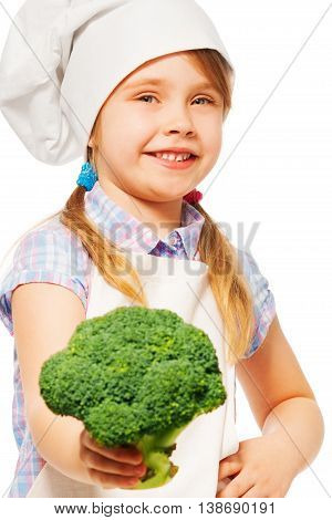Close-up portrait of smiling girl in cook's apron and toque, holding fresh broccoli, isolated on white