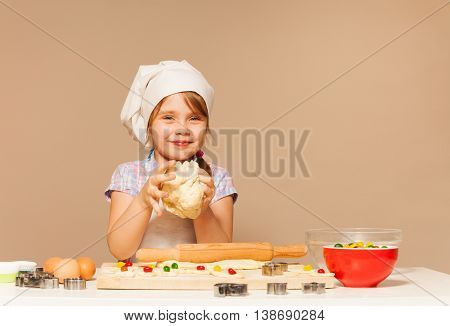 Little smiling baker, girl in apron and toque, kneading the dough for candy filled cookies, standing against the background with copy-space