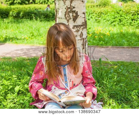 Little girl sitting on the lawn in the park and reading a book