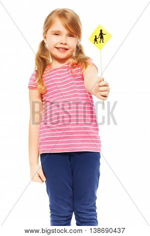 Close-up picture of seven years old girl, holding small Warning Children Crossing road sign in her hand, isolated on white