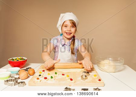 Beautiful girl playing baker, flattening dough with wooden rolling pin, making homemade cookies, background with copy-space