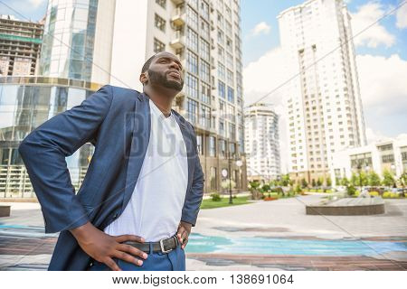 I am ready to work in big city. Young African businessman is standing with arms akimbo. He is looking forward with seriousness