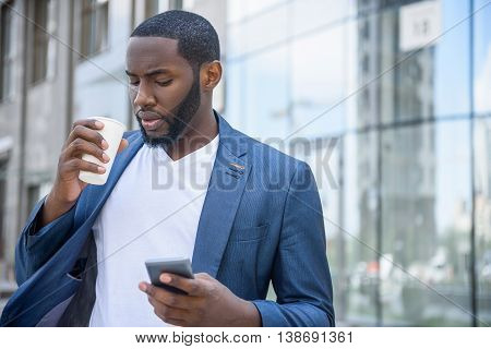 Confident African businessman is drinking coffee with pleasure. He is standing in city and using mobile phone