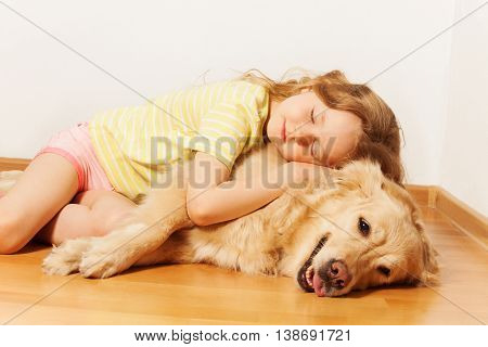 Sleeping five years old girl, lying on the room floor, hugging her Golden Retriever doggy