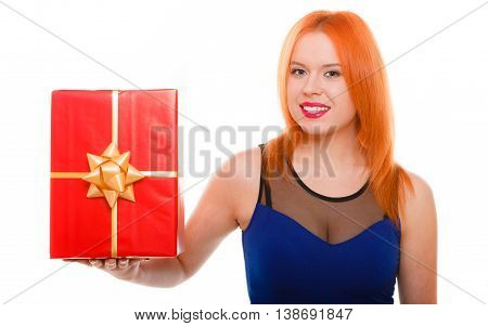 People celebrating holidays love and happiness concept - smiling red head girl in blue dress holds red gift box studio shot isolated. Time gifts