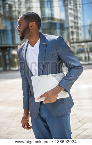 Young businessman is waiting for meeting with hope. He is standing near building with laptop in hands