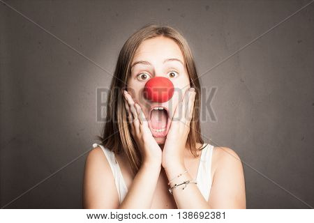 young woman with a clown nose on a grey background