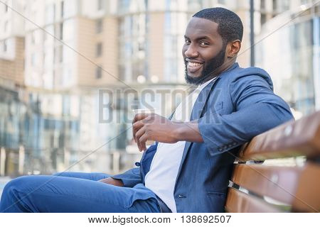 Successful businessman is drinking coffee with enjoyment. He is looking at camera and smiling. Worker is sitting on bench in city