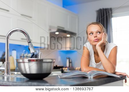 Pretty, young woman in her modern, clean and bright kitchen, uncertain about what to cook (color toned imagey; shallow DOF)