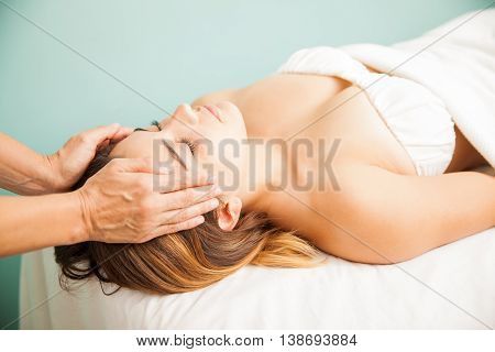Therapist Touching Woman's Temple At A Spa