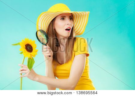 Botanist woman funny face expression in yellow hat examining flower looking through magnifying glass on blue background