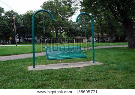 Visitors to the Du Page River waterfront, in Shorewood, Illinois, may sit and relax in a metal swing bench.
