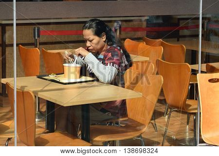 A lonely sad looking woman eating at a quiet eatery
