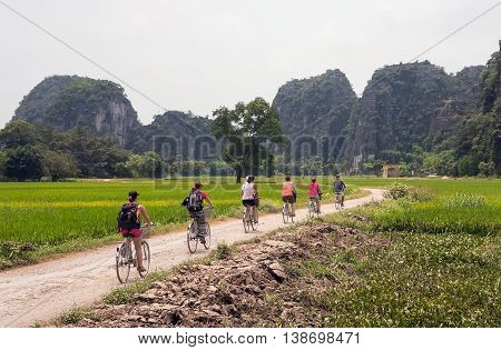 TRANG AN, Ninh Binh, Vietnam, June 18, 2016, tourist groups, cycling, sightseeing, ecotourism, population landscapes Trang An, Ninh Binh, Vietnam, the world natural heritage