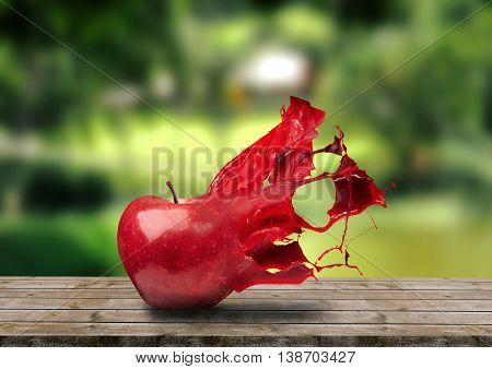 Apple disintegrating in a beautiful splash on a nature background