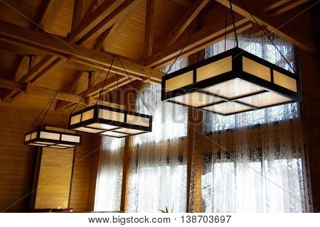 Large glass and wooden chandeliers hanging under the wooden ceiling by chains.