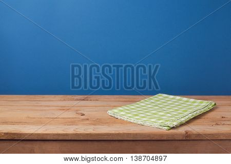 Empty wooden deck table with green checked tablecloth over blue wall background for product montage display