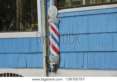 A barbershop pole on the side of a building in Alaska.