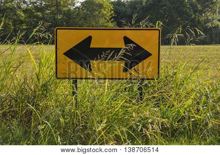 Road sign out in the middle of the country covered by grass.
