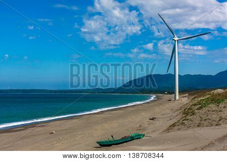 A fishing boat and a windmill on a deserted beach in the Philippines