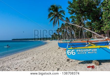 Boats on the shore and a fisherman off the shore of a beach in the Philippines