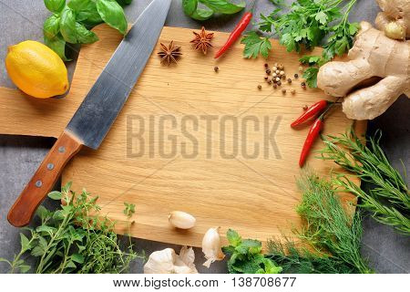 Herbs with a blank chopping board. Space for copy.